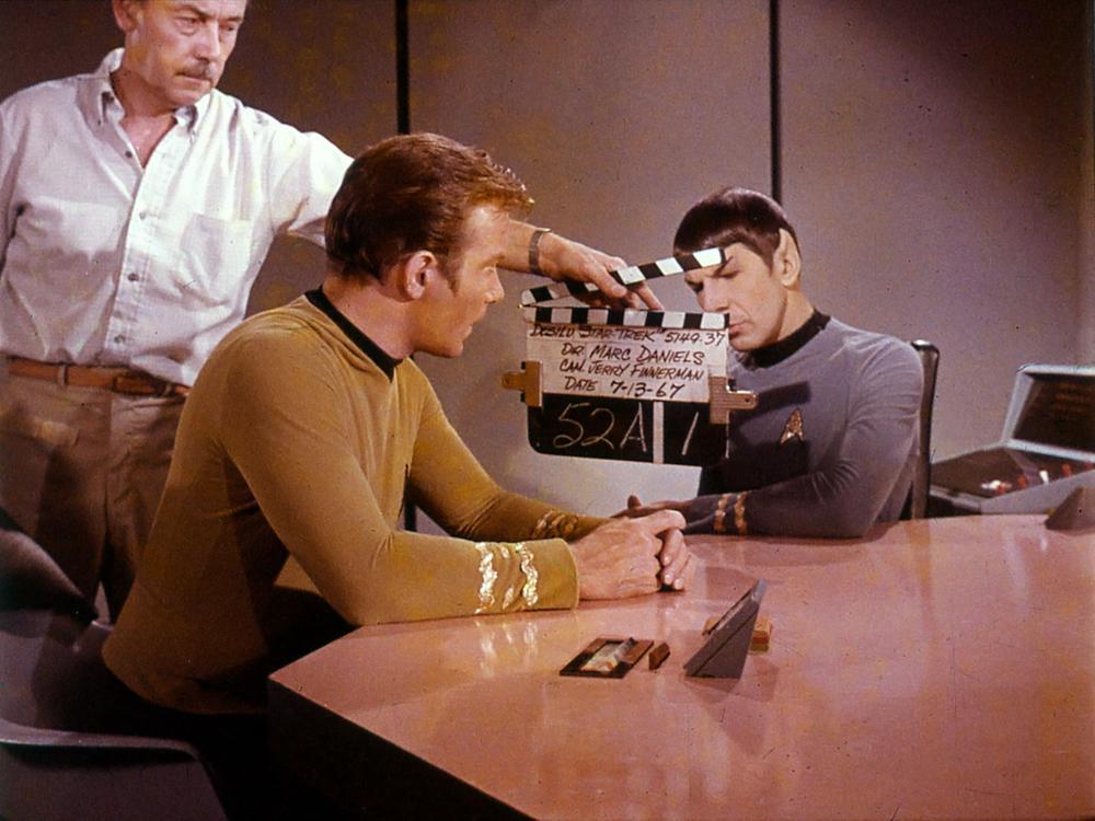 Zwei Männer aus der Serie Raumschiff Enterprise, Kapitän Kirk und Spock, sitzen an einem Tisch. Der Kameraassisten hält eine Filmklappe zwischen sie, weil gleich die nächste Szene gedreht werden soll.