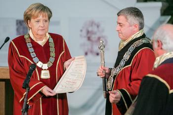 Angela Merkel im Talar erhält eine Ehrendoktorurkunde.
