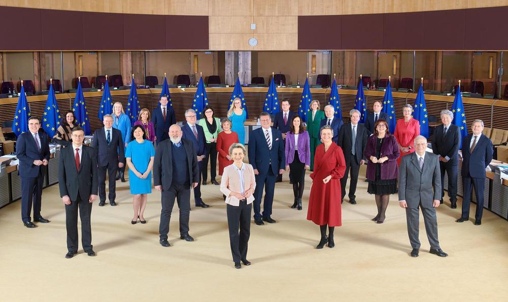 Eine Gruppe von Frauen und Männern steht mit jeweils etwas Abstand in einem großen Raum für ein Gruppenbild.