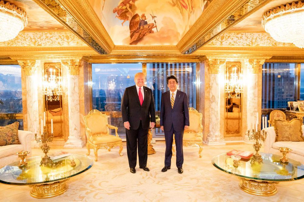 Donald Trump und Shinzo Abe stehen in einem Raum, in dem alle Möbel, Wände und der Boden golden glänzen.
