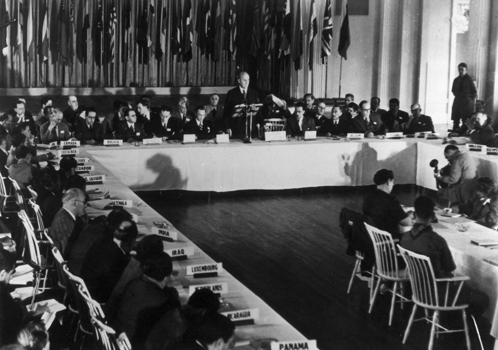 Schwarzweißbild von einer Konferenz. Die Teilnehmer sitzen an einem Tisch in U-Form. Hinter der Kopfseite stehen Flaggen in Rein und Glied.