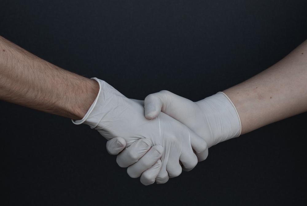 Handschlag in weißen Plastikhandandschuhen; nur Unterarme und Hände sichtbar vor schwarzem Grund.