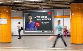 Bahnsteig in einem U-Bahnhof, Menschen eilen an einem Plakat vorbei, auf dem eine Krankenschwester zu sehen ist, darauf der Spruch: Vergiss nie, hier arbeitet ein Mensch!