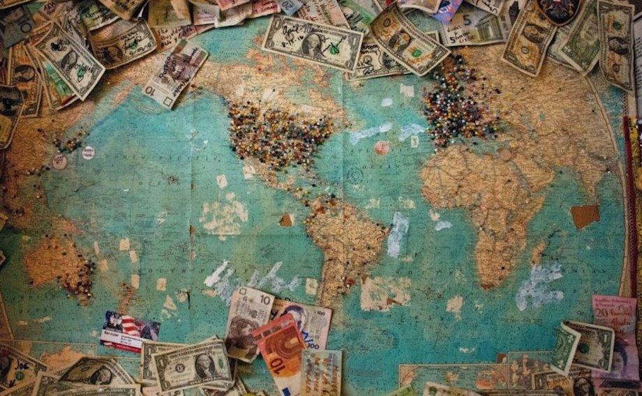 Eine Weltkarte, auf der am Rande ringsum Dollarscheine liegen.