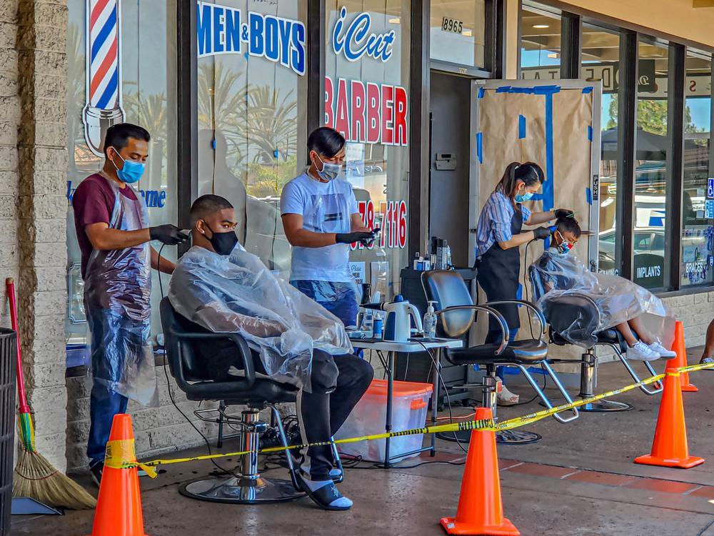 Friseure haben vor ihrem Salon Stühle aufgebaut, an denen sie Kunden die Haare schneiden.