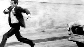 Ein Mann in einem dunklen Anzug rennt vor einem Auto weg, das ihn verfolgt. Bild in Schwarzweiß.