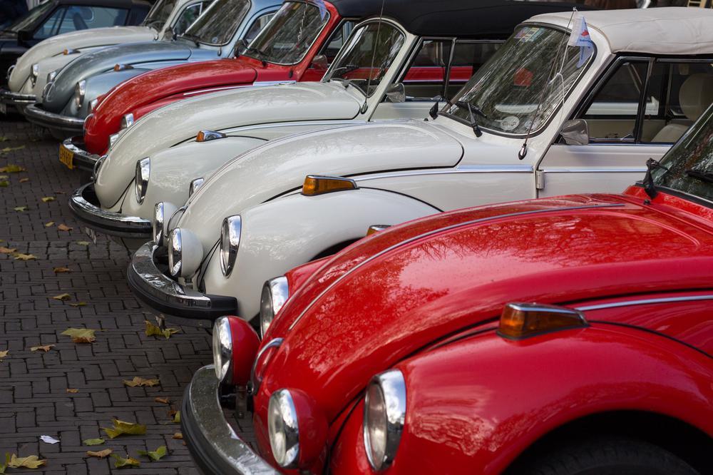 Eine Reihe von bunten VW Käfern nebeneinander von vorne rechts nach hinten links.