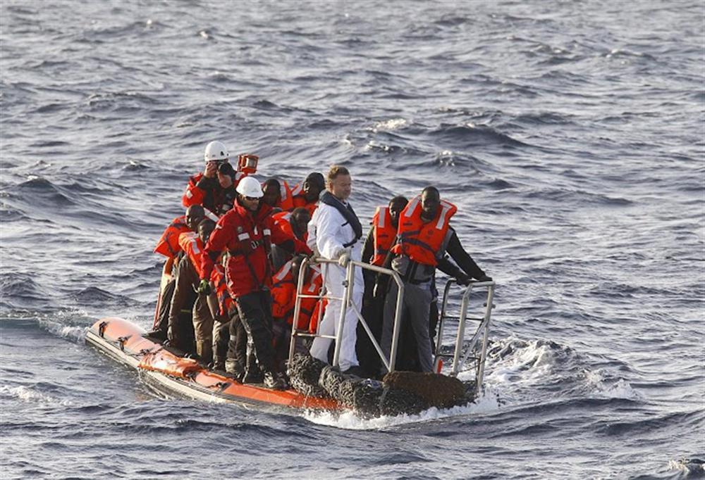Ein Schlauchboot rettet Flüchtlinge, vorne im Boot steht der Kapitän, dahinter sitzen die afrikanischen Flüchtlinge.