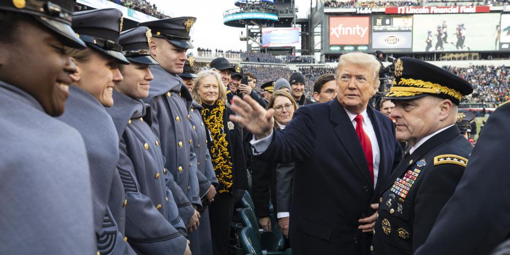 Donald Trump auf der Tribühne eines Football-Stadions mit jungen Soldaten.