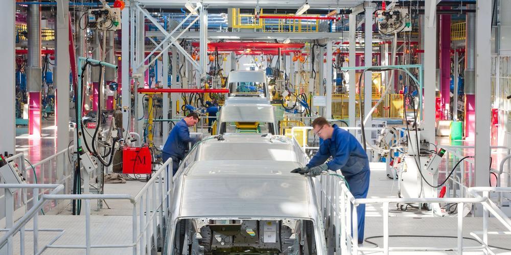 Autofabrik mit Arbeitern an einer Produktionsstraße