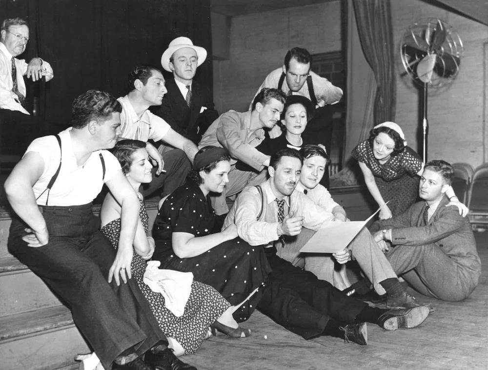 Auf einem Schwarzweißbild sitzt auf einer kleinen Bühne eine Gruppe von jungen Menschen um einen Mann, der ein Blatt Papier in die Höhe hält.