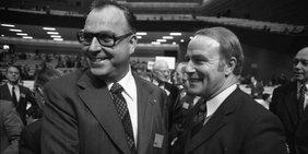 Helmut Kohl und Alfred Dregger reichen sich die Hand, im Hintergrund eine große Halle. Bild in Schwarzweiß.