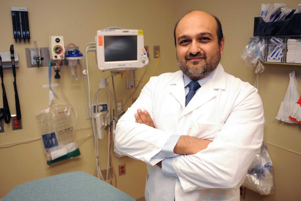 Hasan Gokal steht mit weißem Kittel in seiner Praxis mit medizinischen Geräten im Hintergrund.
