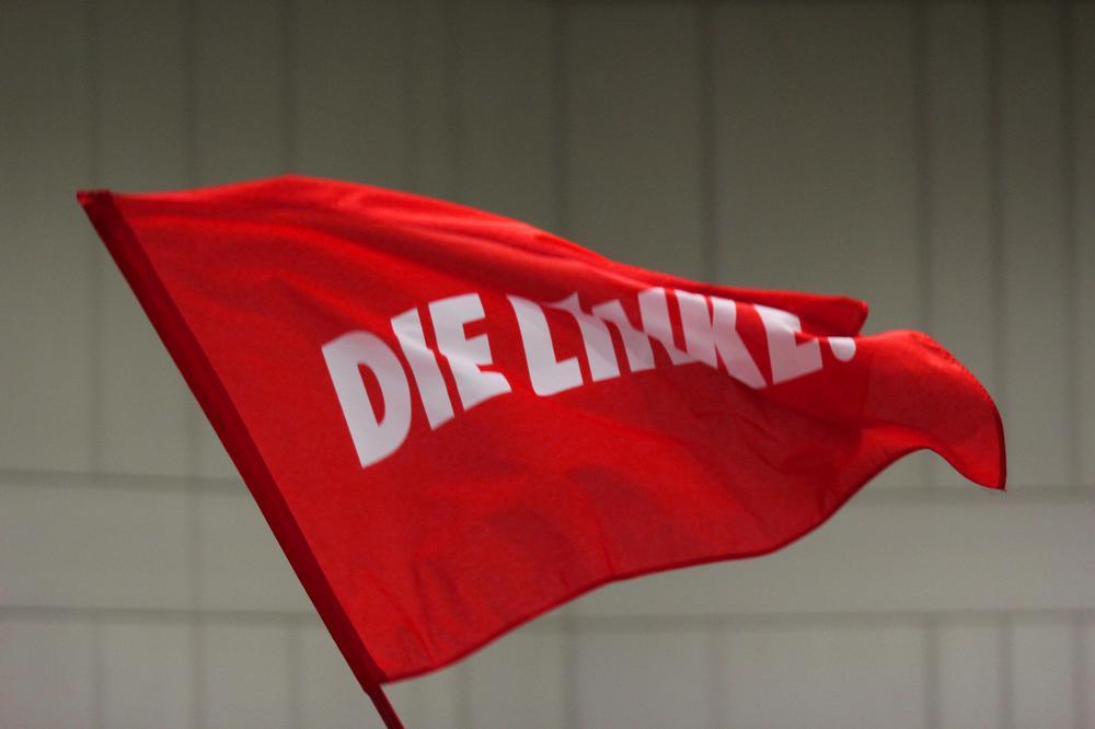 """Eine rote Fahne, auf der """"Die Linke"""" steht, weht im Wind."""
