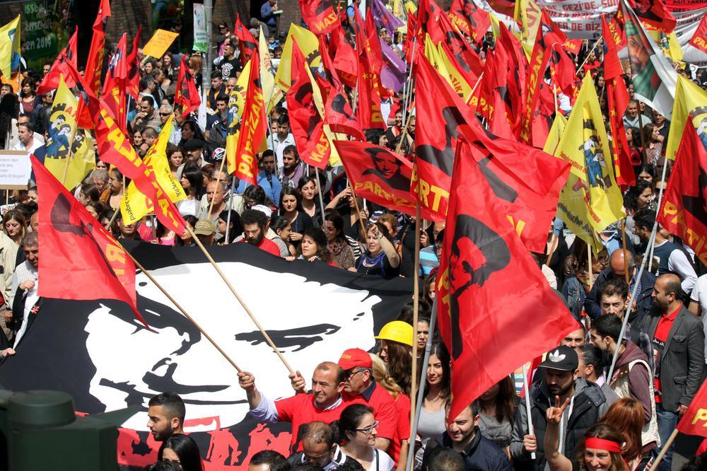 Demonstration auf der viele rote und gelbe Fahnen geschwenkt werden.