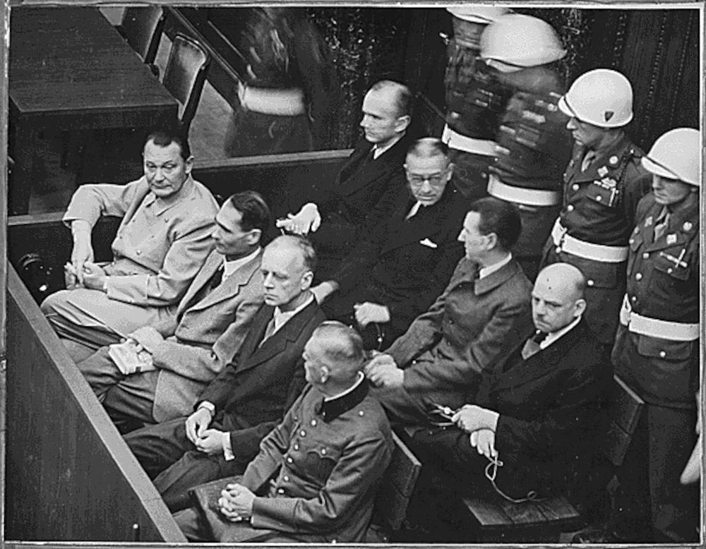 Schwarzweißbild von den zwei hintereinander angeordneten Anklagebänken, gefüllt mit Männern in Anzügen. Dahinter stehen Soldaten mit weißen Helmen.