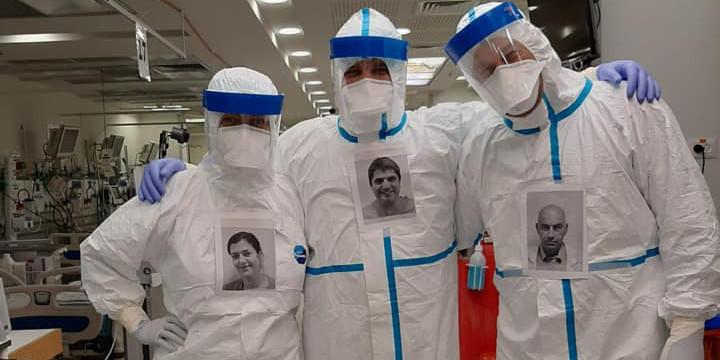 Ärzte und Pfleger in Schutzkleidung haben sich ein Porträtfoto umgehängt, damit Patienten wissen, wie der Mensch hinter der Maske aussieht.