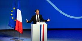 Emmanuel Macron bei einer Rede mit französicher und europäischer Flagge links von ihm.
