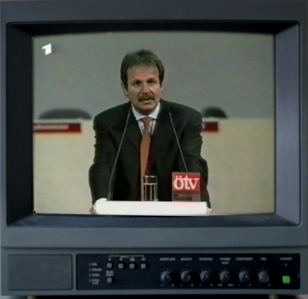 """Frank Bsirske in einem alten Fersehgerät, auf dem eine """"Tagesschau"""" von 2001 läuft."""