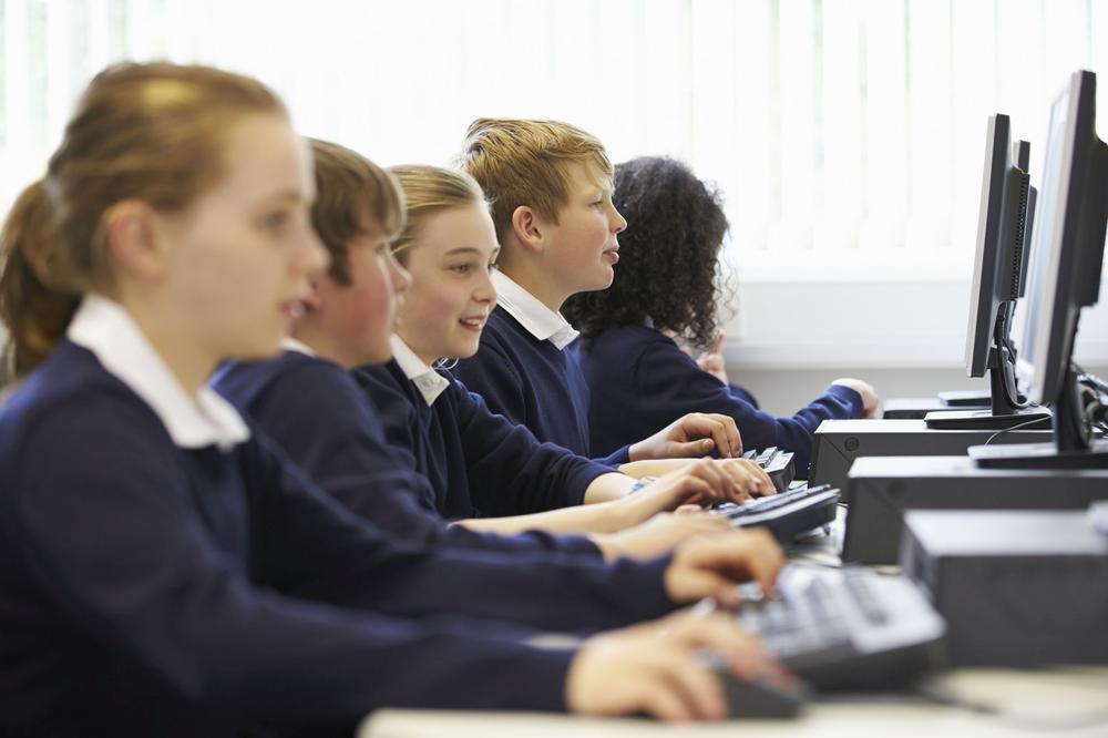 Kinder sitzen in einer Reihe vor Computern in der Schule.