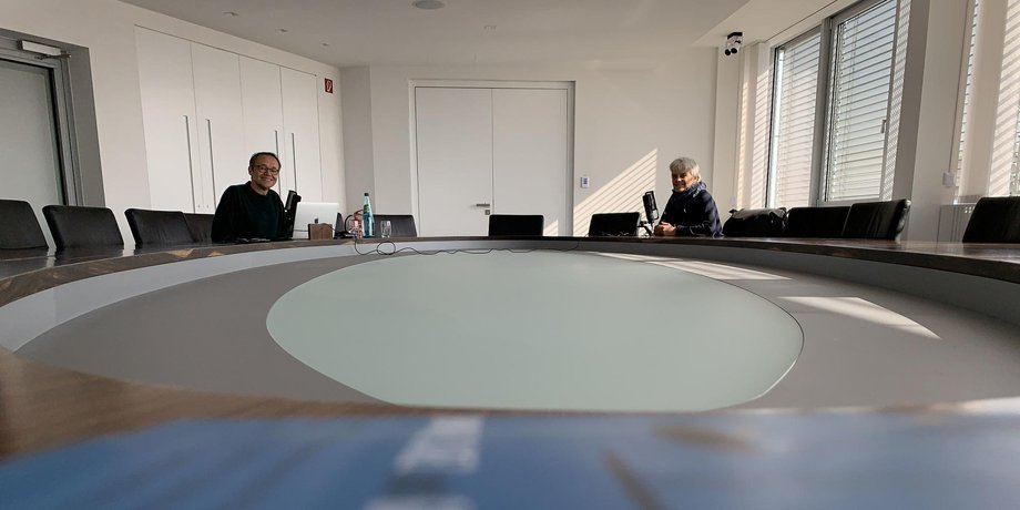 An einem Tisch ziehen weit weg von der Kamera und weit auseinander die Interviewpartner.