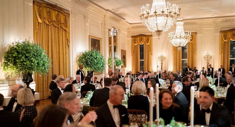 Große runde Tische mit weißen Tischdecken und teuerem Geschirr stehen in einem prächtigen Raum mit Kronleuchtern. An den Tischen sitzen Damen in Abendroben und Männer in Smokings.