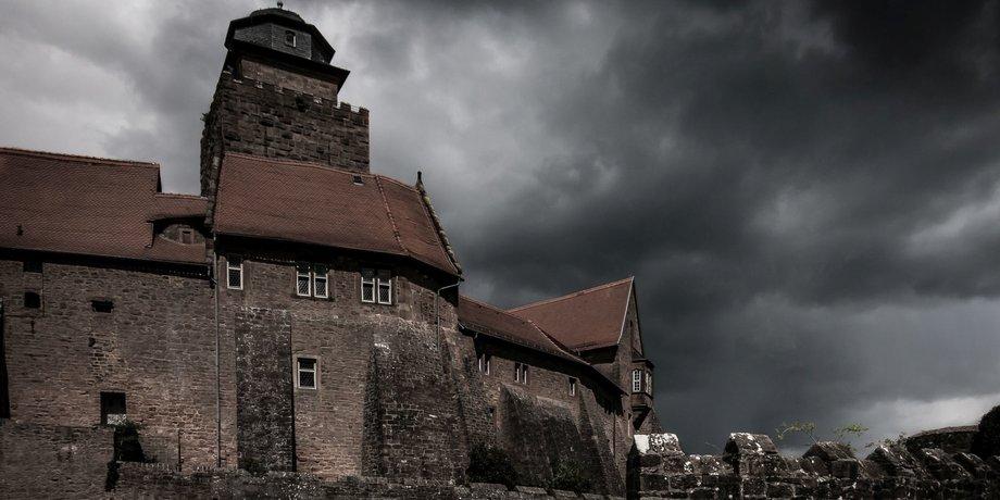 Eine Burg vor Himmel mit düsteren Wolken.