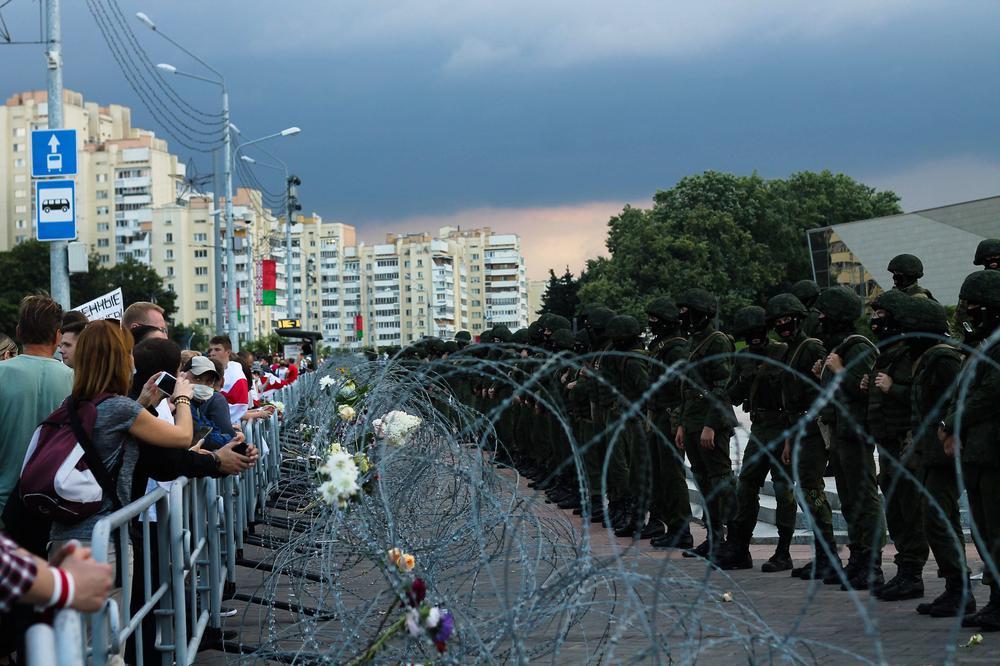 Links stehen Protestanten mit belarussischen Flaggen, rechts Polizisten in Kampfuniform, dazwischen ein Stacheldraht, in dem Blumen stecken.