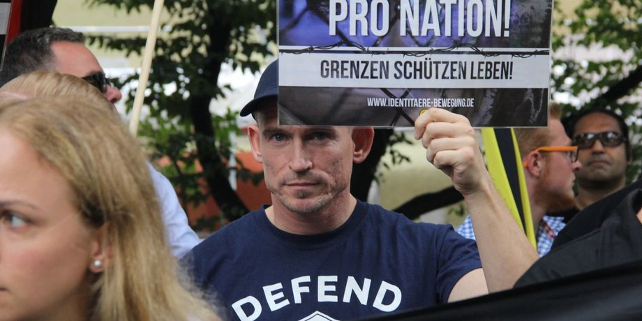"""Kundgebung der Identirären Bewegung, bei der ein man ein kleines Plakat hochhält, auf dem steht: """"Pro Nation! Grenzen schützen leben!"""""""