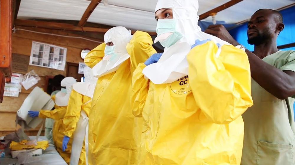 Mehrere Menschen tragen gelbe Schutzkleidung von Kopf bis Fuß und stehen nebeneinander, während sie Gesichtschutzmasken anlegen.