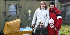 Familie mit Kindern vor Bauwagen