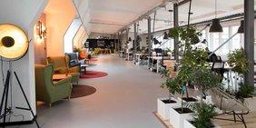 Lang nach hinten sich ziehendes Büro mit Schreibtischen für mehrere Personen auf der rechten Seite. Links stehen Sessel an der Wand.