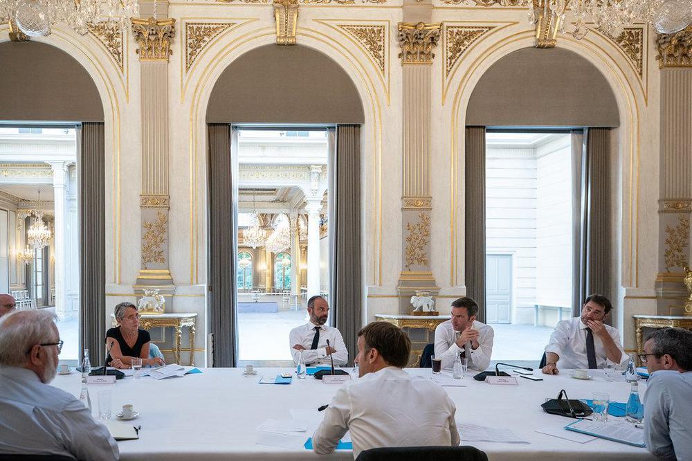 Frankreichs Präsident Macron (vorne Mitte) sitzt mit einem Kabinett an einem sehr großen Tisch, alle weit auseinander, in einem prächtigen Raum mit goldenen Leuchtern.