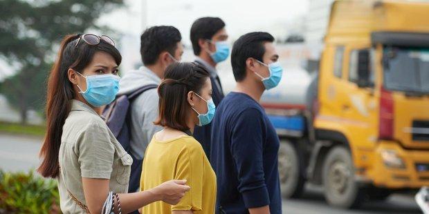 Menschen mit Atemmasken stehen am Rand einer Straße.
