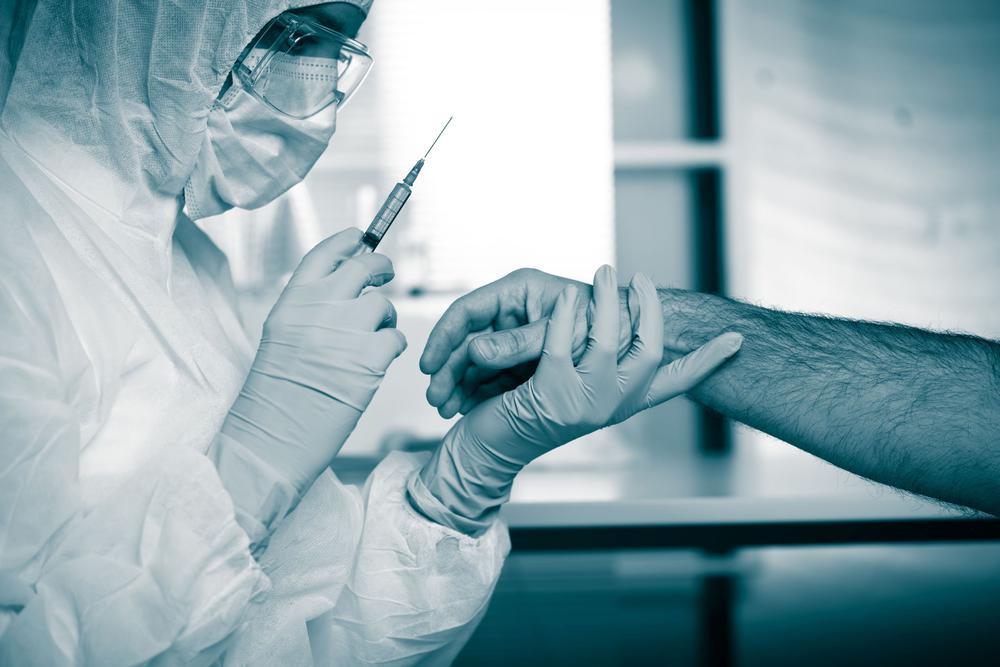 Ein Arzt in Schutzkleidung mit Gesichtsmaske hält eine Spritze an den Arm eines Mannes.