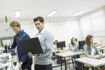 Frauen und Männer werden an Computern unterrichtet