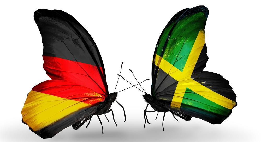 Zwei Schmetterlinge von der Seite, einer mit Flügel in den Farben der deutschen Flagge, einer in denen der jamaikanischen.