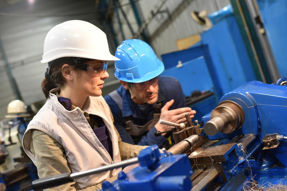 Eine Frau und ein Mann stehen in blauer Arbeitskleidung an einer metallverarbeitenden Maschine.