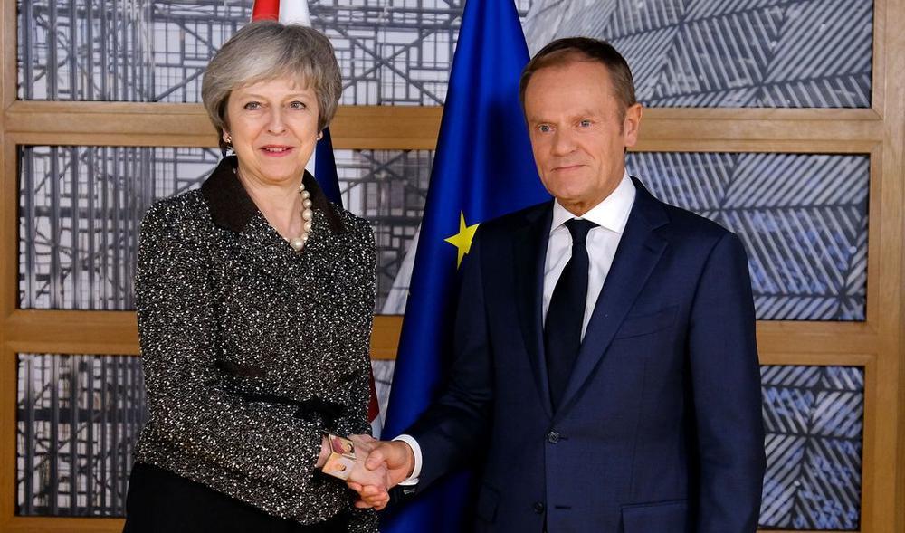 Theresa May und Donald Tusk geben sich die Hand.