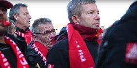 Demonstranten mit roten Schals der IG Metall blicken ernst.