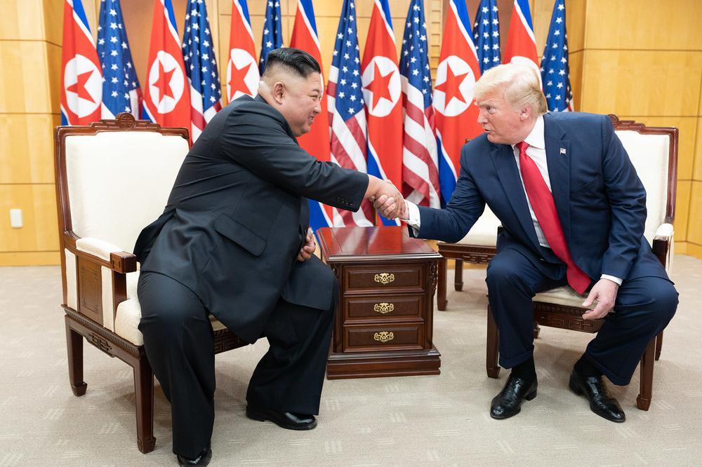 Kim Jong-Un und Donald Trump sitzen auf Sesseln vor Flaggen ihrer Länder.