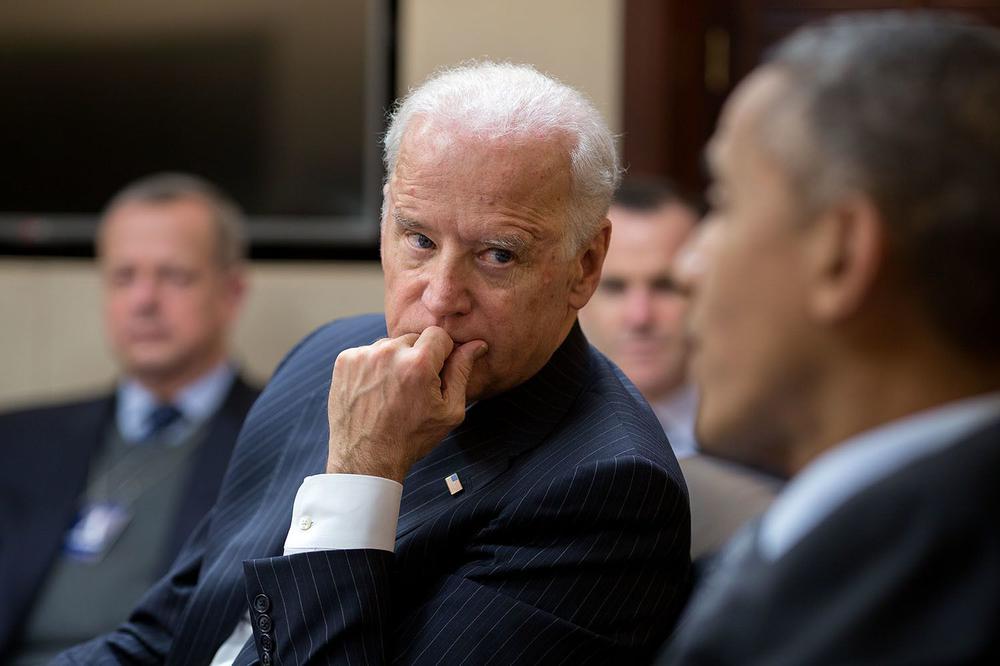 Joe Biden sitzt neben Barack Obama und hört ihm aufmerksam zu.