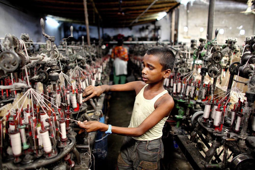 Ein Kind arbeitet in einer Spinnerei und fädelt Fäden auf.