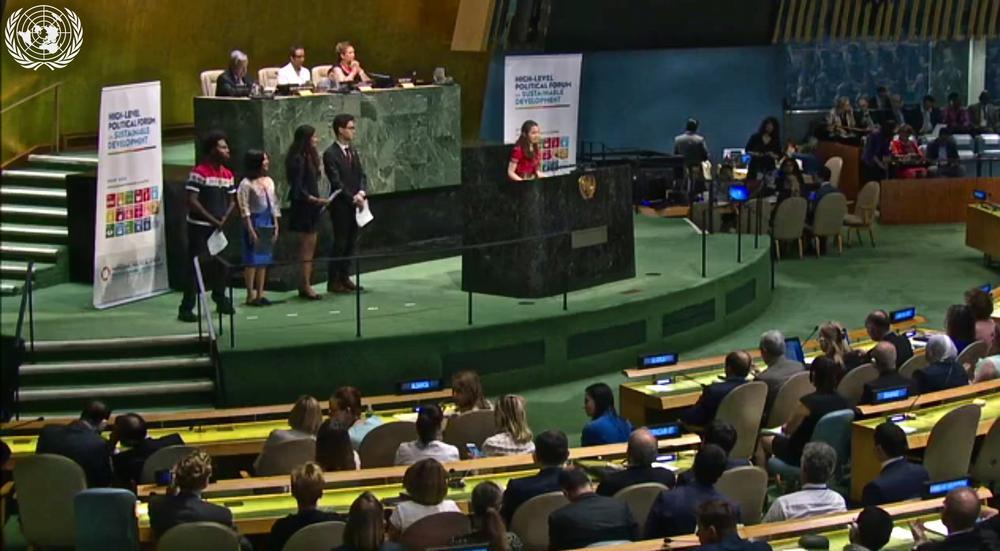 Eine junge Frau steht am Pult im Raum für die UN-Vollversammlungen und spricht.