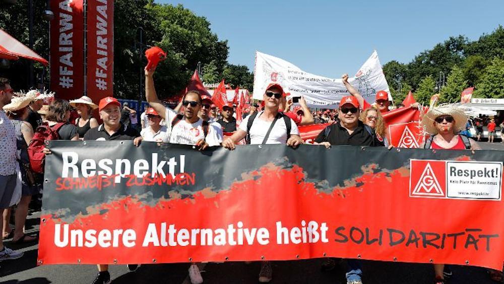 Menschen bei einer Demo tragen ein rotes Transparent vor sich, auf dem steht: Respekt schweißt zusammen. Unsere Alternative heißt: Solidarität. Kein Platz für Rassismus.
