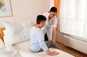 Eine Pflegerin hilft einer alten Frau beim Aufstehen aus dem Bett.