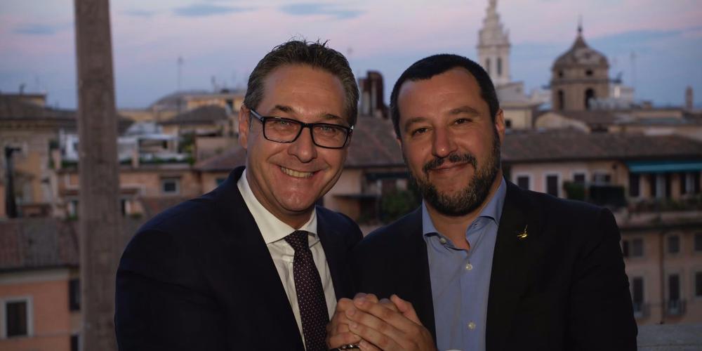 Matteo Salvini und Heinz-Christian Strache lachen in die Kamera, während sie ihre Hände ineinadner verschlingen.