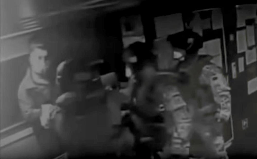Bild einer Überwachungskamera, auf dem Soldaten in Kampfuniform im Vordergrund stehen, rechts von ihnen etwas weiter hinten im Raum steht ein Mann. Alle tragen Gesichtsmasken.
