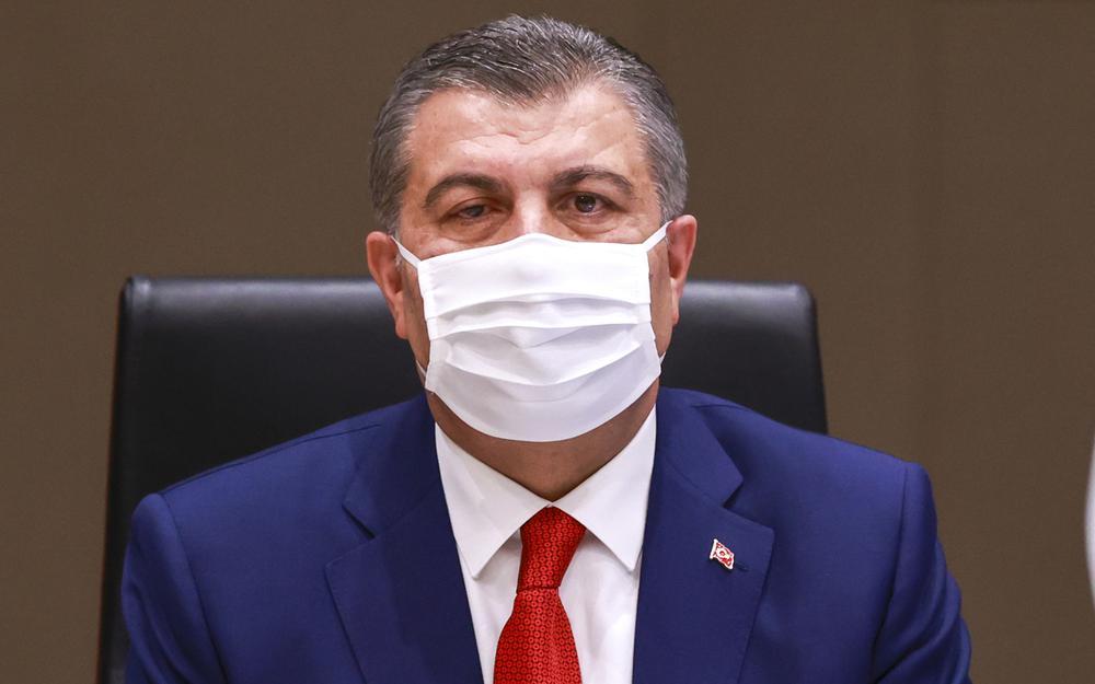 Der türkische Gesundheitsminister sitzt am Schreibtisch, im blauen Anzug und mit weißer Gesichtsmaske.