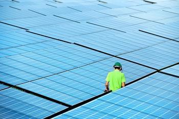 Sonnenkollektoren und ein Mitarbeiter mit gelbem Helm, der dazwischen entlangt geht.